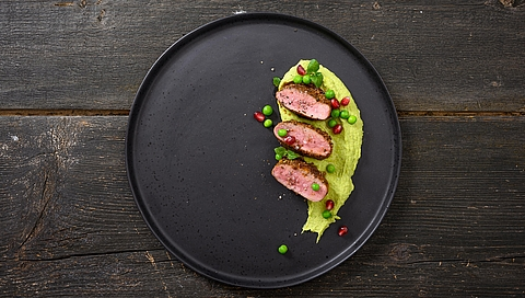 Ras el hanout spiced saddle of lamb with pea and mint houmous and pomegranate