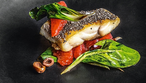 Hake in a chia seed crust with pink grapefruit, taggiasca olives and chard