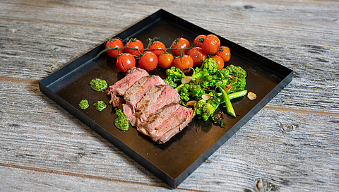 Entrecôte steak with broccolini, almonds, grilled cherry tomatoes and herbal salsa