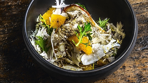 Cauliflower and orange salad dusted with black tea and served with bread crisps