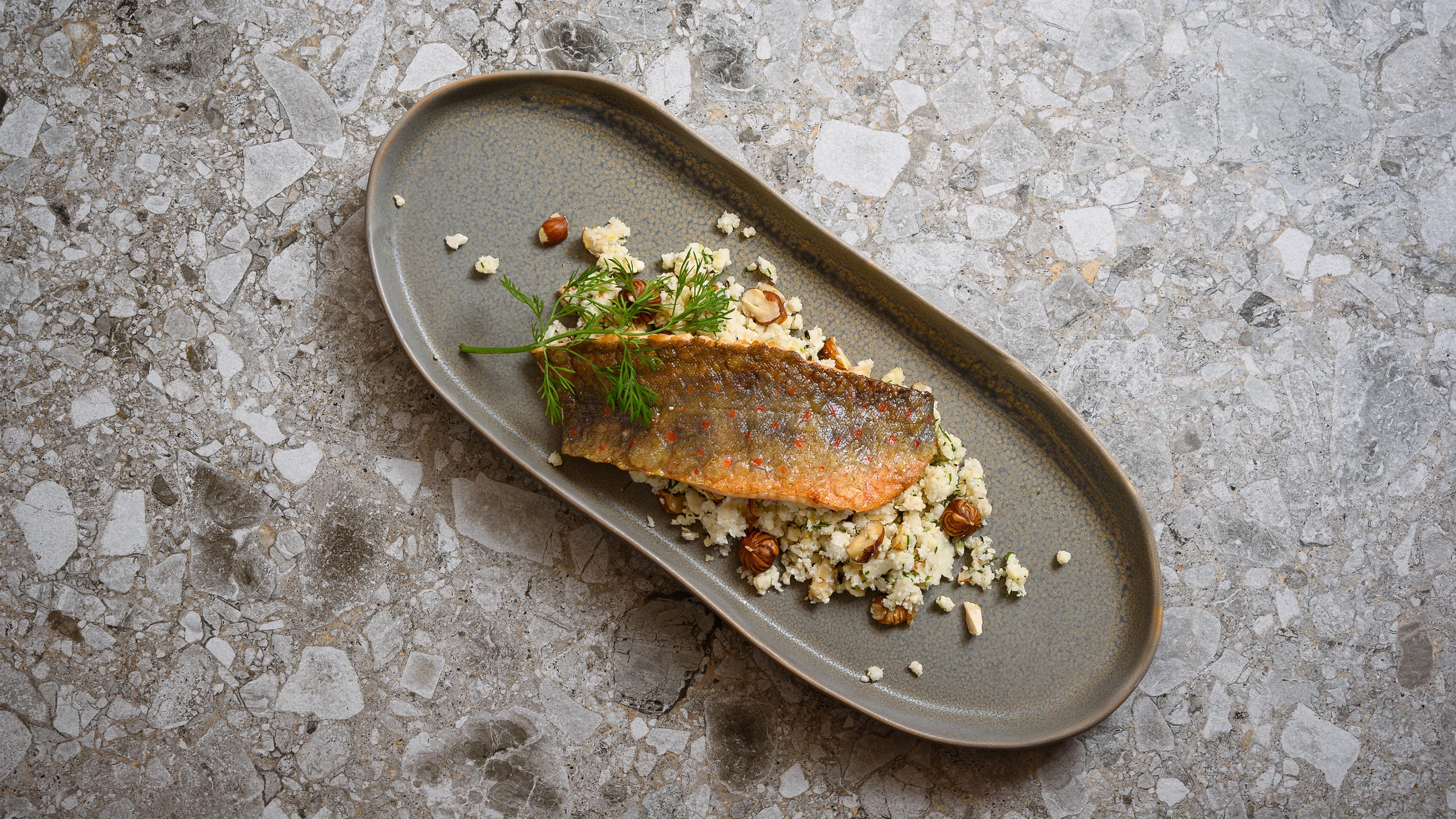 Char on a bed of cauliflower couscous and hazelnuts